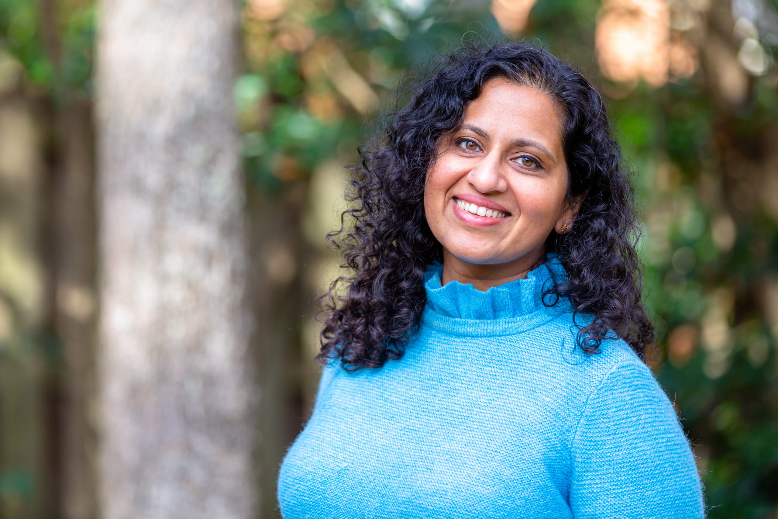 Picture of Aparna Polavarapu wearing a blue sweater, standing in front of trees